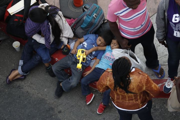 People wait to apply for asylum in the United States along the border, Tuesday, July 16, 2019, in Tijuana, Mexico. Dozens of immigrants lined up Tuesday at a major Mexico border crossing, waiting to learn how the Trump administration's plans to end most asylum protections would affect their hopes of taking refuge in the United States. (AP Photo/Gregory Bull)