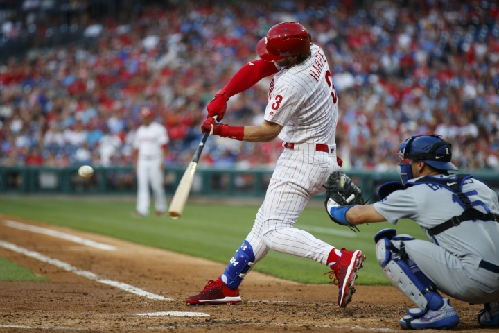 Philadelphia Phillies' Bryce Harper, left, hits a three-run home run off Los Angeles Dodgers starting pitcher Walker Buehler during the second inning of a baseball game, Tuesday, July 16, 2019, in Philadelphia. At right is catcher Austin Barnes. (AP Photo/Matt Slocum)