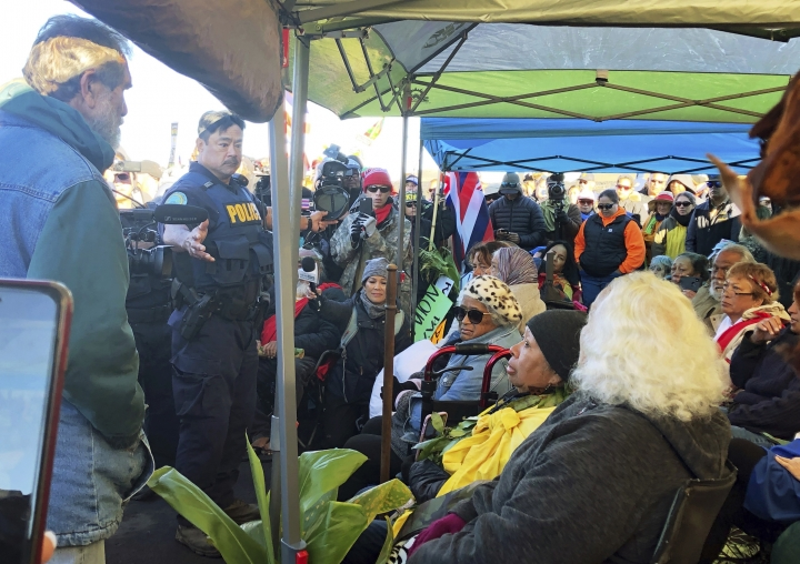 Officers from the Hawaii Department of Land and Natural Resources prepare to arrest protesters, many of them elderly, who are blocking a road to prevent construction of a giant telescope on a mountain that some Native Hawaiians consider sacred, on Mauna Kea on the Big Island of Hawaii Wednesday, July 17, 2019. Police were taking away about 30 elders, who were prepared to be arrested. Protest leader Kealoha Pisciotta says hundreds of demonstrators moved aside to allow the elders to be taken away. (Cindy Ellen Russell/Honolulu Star-Advertiser via AP)