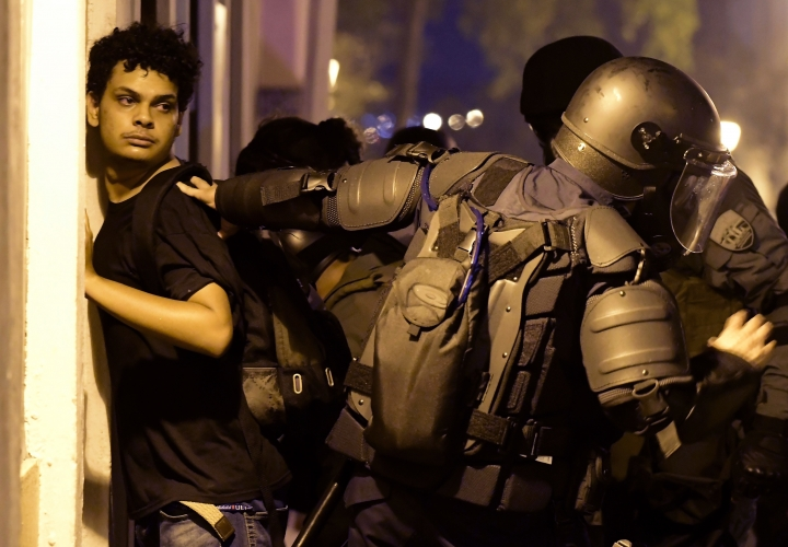 Police arrest a demonstrator during clashes in San Juan, Puerto Rico, Wednesday, July 17, 2019. Thousands of people marched to the governor's residence in San Juan on Wednesday chanting demands for Gov. Ricardo Rossello to resign after the leak of online chats that show him making misogynistic slurs and mocking his constituents. (AP Photo/Carlos Giusti)