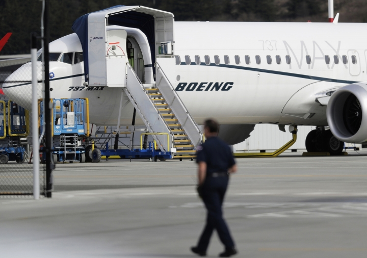 FILE - In this March 14, 2019, file photo, a worker walks next to a Boeing 737 MAX 8 airplane parked at Boeing Field in Seattle. Boeing said Thursday, July 18, it will take a $4.9 billion charge to cover possible compensation to airlines whose Max jets remain grounded after two deadly accidents. (AP Photo/Ted S. Warren, File)