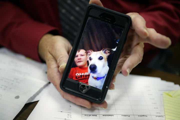Jackson County Municipal Court Judge Mark T. Musick displays an image of Brandon, a young man he helped raise as a son, as he sits at his bench, Wednesday, July 17, 2019, in Jackson, Ohio. Musick presides over the local drug court in an area heavily damaged by the opioid epidemic. The image was sent by Brandon hours before his fatal overdose on opioids and serves as the home screen image on the judge's phone. (AP Photo/John Minchillo)