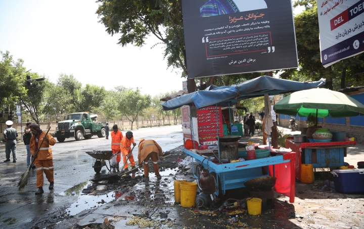 Workers clean the site of an explosion in Kabul, Afghanistan, Friday, July 19, 2019. A powerful bomb exploded outside the gates of Kabul University in the Afghan capital on Friday, according to police and health officials. (AP Photo)