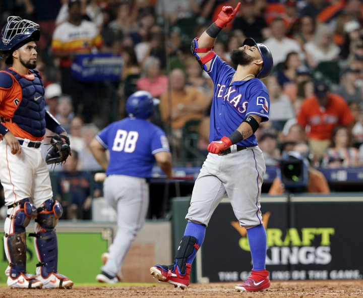 Texas Rangers Rougned Odor points skyward as he crosses the plate after his home run, next to Houston Astros catcher Robinson Chirinos during the sixth inning of a baseball game Friday, July 19, 2019, in Houston. (AP Photo/Michael Wyke)