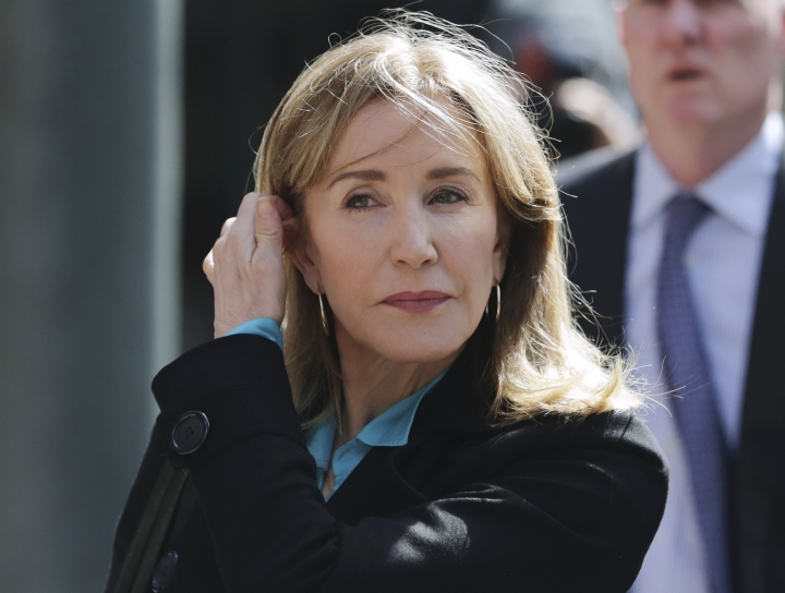 "FILE - In this April 3, 2019 file photo, actress Felicity Huffman arrives at federal court in Boston to face charges in a nationwide college admissions bribery scandal. Huffman's co-stars in a new Netflix movie say they found her remorseful about her role in a college admissions scandal. Huffman didn't meet reporters to promote the film ""Otherhood,"" which premieres on Netflix on Aug. 2. She pleaded guilty in May to paying $15,000 to a college admissions consultant to have a procter correct her daughter's answers on the SAT. (AP Photo/Charles Krupa, File)"