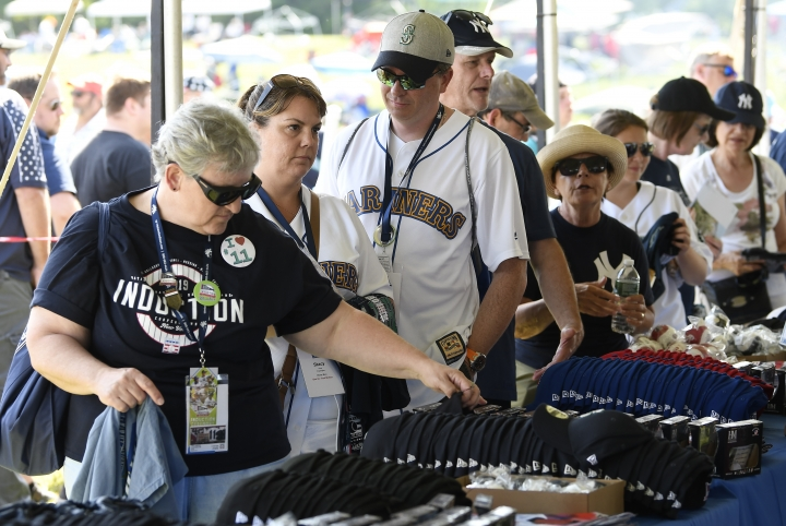 Gail Edmund of Northbound, Wash., left, purchases baseball souvenirs for friends before a Baseball Hall of Fame induction ceremony at the Clark Sports Center on Sunday, July 21, 2019, in Cooperstown, N.Y. (AP Photo/Hans Pennink)