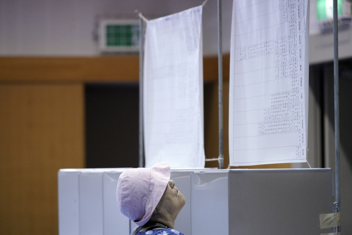 A voter looks at a list of candidates before casting her ballot in the upper house elections at a polling station in Tokyo Sunday, July 21, 2019. Voting started Sunday morning for the upper house elections where Japanese Prime Minister Shinzo Abe's ruling coalition is seen to retain majority, according to local media report. (AP Photo/Eugene Hoshiko)