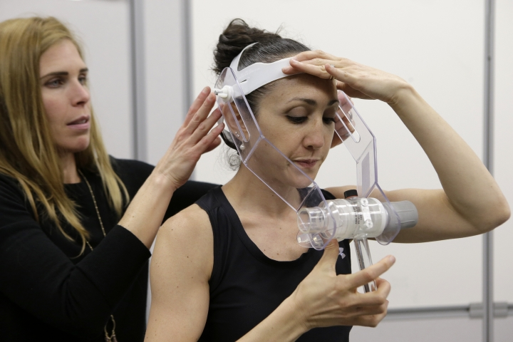 In this April 23, 2019 photo, nutritional physiologist Holly McClung, left, assists research scientist Leila Walker, right, as they demonstrate equipment designed to evaluate fitness levels of female soldiers, not shown, who have joined elite fighting units such the Navy Seals, at the U.S. Army Research Institute of Environmental Medicine, at the U.S. Army Combat Capabilities Development Command Soldier Center, in Natick, Mass. (AP Photo/Steven Senne)