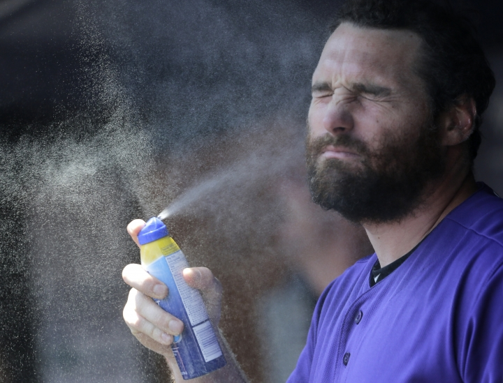 Colorado Rockies' Daniel Murphy applies sunscreen before a baseball game against the New York Yankees at Yankee Stadium, Sunday, July 21, 2019, in New York. (AP Photo/Seth Wenig)