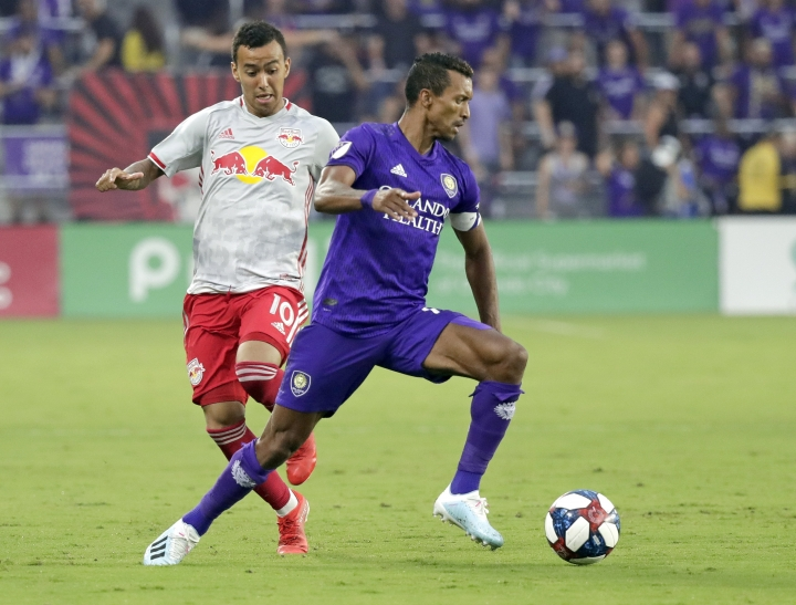 Orlando City's Nani, right, moves the ball past New York Red Bulls' Kaku during the first half of an MLS soccer match, Sunday, July 21, 2019, in Orlando, Fla. (AP Photo/John Raoux)