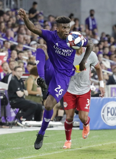 Orlando City's Carlos Ascues (26) gets control of a pass in front of New York Red Bulls' Amro Tarek (3) during the first half of an MLS soccer match, Sunday, July 21, 2019, in Orlando, Fla. (AP Photo/John Raoux)