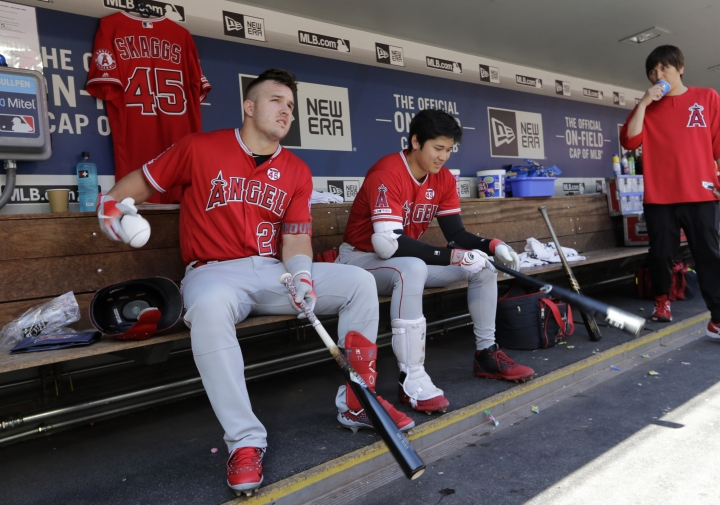 Los Angeles Angels' Mike Trout, left, and Shohei Ohtani sit together in the dugout in the third inning of a baseball game against the Seattle Mariners, Sunday, July 21, 2019, in Seattle. (AP Photo/Elaine Thompson)