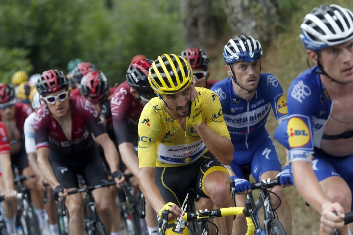 France's Julian Alaphilippe wearing the overall leader's yellow jersey rides in the pack with Britain's Geraint Thomas, left, during the fifteenth stage of the Tour de France cycling race over 185 kilometers (114,95 miles) with start in Limoux and finish in Prat d'Albis, France, Sunday, July 21, 2019. (AP Photo/Thibault Camus)