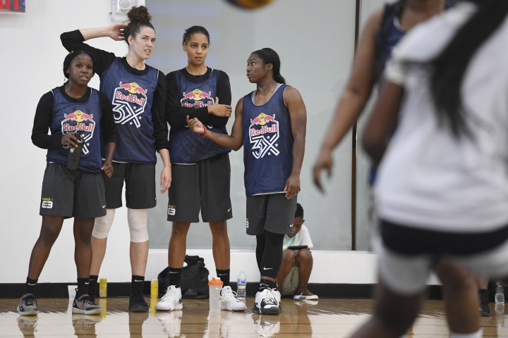 In this photo taken July 20, 2019, Force 10 teammates, from left to right, Alexis Peterson, Megan Huff, Cierra Burdick and Linnae Harper watch a basketball game during the Red Bull 3X tournament in the Brooklyn borough of New York. The Seattle Storm ownership group put together a pilot program with Peterson, Burdick, Harper and Huff to travel the country and play in USA Basketball Red Bull 3x3 Tournaments. (AP Photo/Sarah Stier)