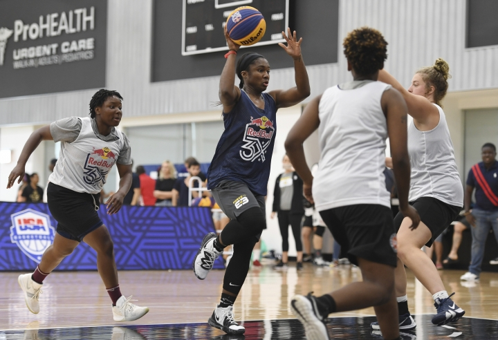 In this photo taken July 20, 2019, Force 10's Linnae Harper, center, dribbles toward the basket against opposing team members during the Red Bull 3X basketball tournament in the Brooklyn borough of New York. The Seattle Storm ownership group put together a pilot program with Alexis Peterson, Cierra Burdick, Harper and Megan Huff to travel the country and play in USA Basketball Red Bull 3x3 Tournaments. (AP Photo/Sarah Stier)