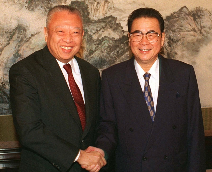 CORRECTS AGE TO 90, INSTEAD OF 91 - FILE - In this Dec. 10, 1997, file photo released by CHina's Xinhua News Agency, then Hong Kong leader Tung Chee-hwa and then Chinese Premier Li Peng shake hands at the start of their meeting in Beijing. Li Peng, a former hard-line Chinese premier best known for announcing martial law during the 1989 Tiananmen Square pro-democracy protests, has died. He was 90. (Xinhua via AP, File)