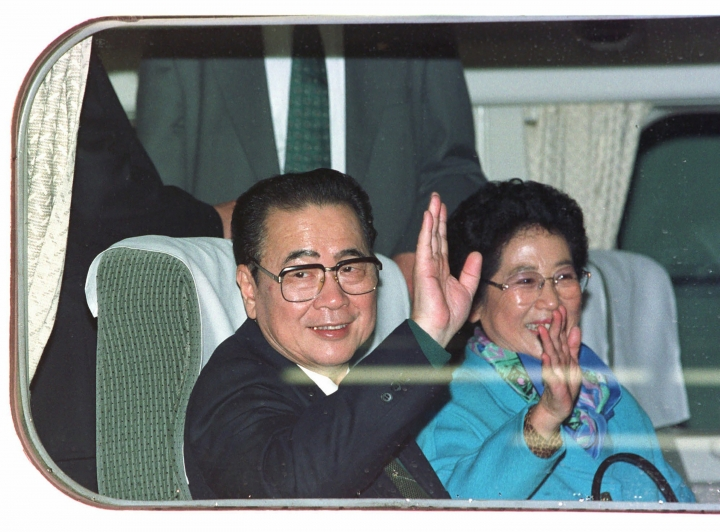 CORRECTS AGE TO 90, INSTEAD OF 91 - FILE - In this Nov. 13, 1997, file photo, then Chinese Premier Li Peng, left, and his wife Zhu Lin wave from a bullet train window before they leave for Odawara City, west of Tokyo, at the Tokyo Central station. Li Peng, a former hard-line Chinese premier best known for announcing martial law during the 1989 Tiananmen Square pro-democracy protests, has died. He was 90. (AP Photo/Shizuo Kambayashi, File)