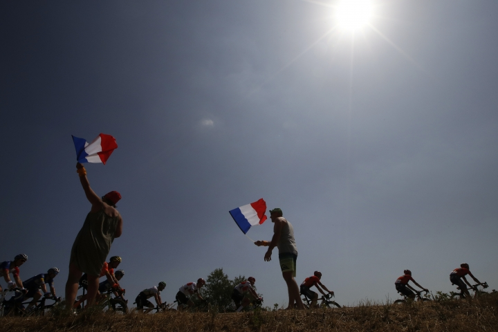 Spectators hold French flag as they cheer the riders during the sixteenth stage of the Tour de France cycling race over 117 kilometers (73 miles) with start and finish in Nimes, France, Tuesday, July 23, 2019. (AP Photo/ Christophe Ena)