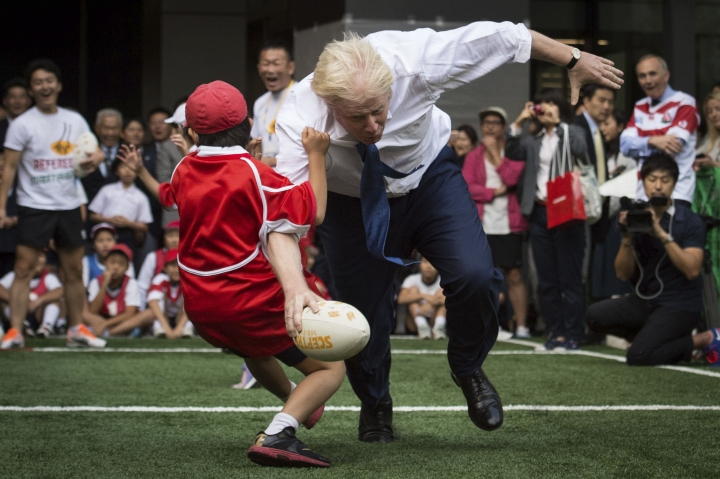FILE - In this Oct. 15, 2015 file photo, Boris Johnson takes part in a Street Rugby tournament in a Tokyo street. Britain's new top diplomat is shaggy-haired, Latin-spouting Boris Johnson, who in recent months has made insulting and vulgar comments about the presidents of the United States and Turkey. (Stefan Rousseau/PA via AP)