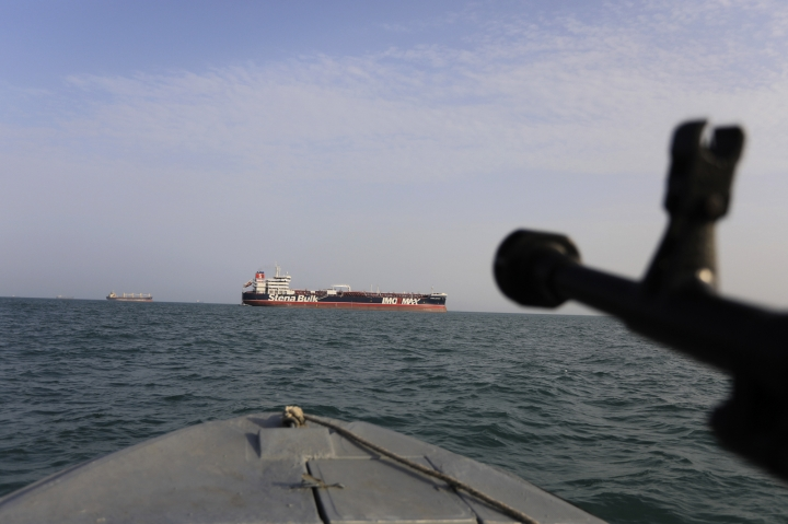 In this Sunday, July 21, 2019 photo, a speedboat of Iran's Revolutionary Guard trains a weapon toward the British-flagged oil tanker Stena Impero, which was seized in the Strait of Hormuz on Friday by the Guard, in the Iranian port of Bandar Abbas. Global stock markets were subdued Monday while the price of oil climbed as tensions in the Persian Gulf escalated after Iran's seizure of a British oil tanker on Friday. (Morteza Akhoondi/Tasnim News Agency via AP)