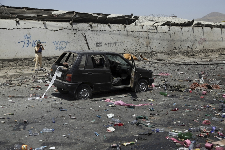 A damaged civilian car is seen at the site of a suicide attack in Kabul, Afghanistan, Thursday, July 25, 2019. Three bombings struck the Afghan capital on Thursday, killing at least eight people, including five women and one child, officials said Thursday. (AP Photo/Rahmat Gul)