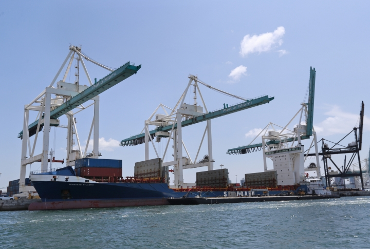 In this Wednesday, July 24, 2019 photo, the container ship Seaboard Atlantic is shown docked at PortMiami in Miami. The government says the U.S. economy grew more slowly in 2018 than it previously estimated, downgrading its estimate from 3% to 2.5%. President Donald Trump had frequently boasted of the 3% growth figure as evidence that his policies invigorated the economy. (AP Photo/Wilfredo Lee)