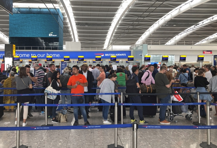 Queues in Terminal 5 at Heathrow airport, Friday July 26, 2019. Travelers are facing a second day of disruption in Britain after record breaking July temperatures gave way to thunderstorms. The heat eased Friday, but Heathrow, Europe's biggest airport, was forced to cancel or delay flights amid severe weather conditions. (Steve Parsons/PA via AP)