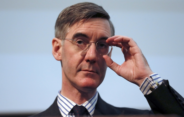 """FILE - In this Wednesday, Jan. 23, 2019 file photo, British lawmaker Jacob Rees-Mogg gestures as he speaks at a meeting for eurosceptic think tank The Bruges group, in London. The new leader of Britain's House of Commons has some old-fashioned rules for staff, banning metric measurements and ordering men to be addressed as """"esquire."""" A memo for staff of Conservative lawmaker Jacob Rees-Mogg published Friday, July 26 says men without aristocratic titles should get the suffix """"Esq."""" in correspondence. (AP Photo/Alastair Grant, file)"""