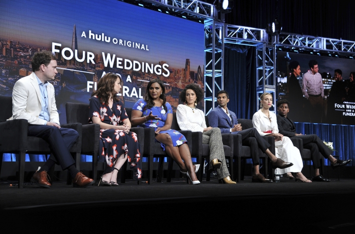 """Co-creator/executive producer Matt Warburton, from left, showrunner/executive producer Tracey Wigfield, co-creator/executive producer Mindy Kaling, Nathalie Emmanuel, Nikesh Patel, Rebecca Rittenhouse and Brandon Mychal Smith participate in Hulu's """"Four Weddings and a Funeral"""" panel at the Television Critics Association Summer Press Tour on Friday, July 26, 2019, in Beverly Hills, Calif. (Photo by Richard Shotwell/Invision/AP)"""