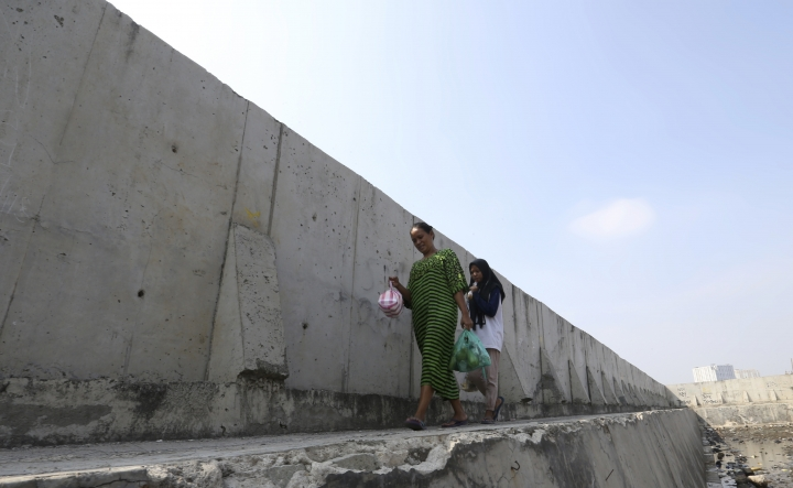 Women walk near a giant sea wall used as a barrier to prevent sea water from flowing into land and cause flooding in Jakarta, Indonesia, Saturday, July 27, 2019. Indonesia's President Joko Widodo said in an interview that he wants to see the speedy construction of the giant sea wall to save the low-lying capital of Jakarta from sinking under the sea, giving renewed backing to a long-delayed multi-billion-dollar mega project. (AP Photo/Achmad Ibrahim)