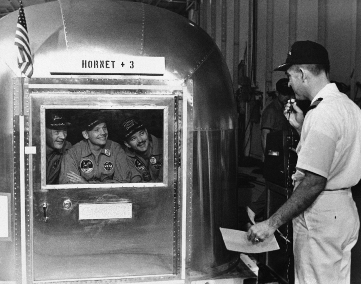 FILE - In this July 25, 1969, file photo, Capt. Carl Seiberlich, commander of the carrier Hornet, right, says goodbye to Apollo 11 astronauts Edwin Aldrin Jr., from left, Neil Armstrong and Michael Collins in Honolulu, Hawaii, before they were taken in their quarantine van to a waiting cargo plane to be flown to Houston, Texas. This week marked the 50th anniversary of the moon landing, but after those historic first steps NASA still had to get the three astronauts safely back to Earth, and the waters off Hawaii are where the cone-shaped spacecraft splashed down. (AP Photo, File)