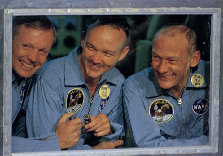 "FILE - In this July 24, 1969, file photo, Apollo 11 astronauts, Neil Armstrong, left, Michael Collins, center, and Edwin ""Buzz"" Aldrin smile as they answer questions from quarantine in an isolation unit aboard the USS Hornet after splashdown and recovery. The Honolulu Star-Advertiser reported Wednesday, July 24, 2019, the 50th anniversary of the astronaut's return to Earth, that the crew hit the atmosphere at 25,000 mph, creating a fireball that was visible to the crew of the waiting recovery aircraft carrier USS Hornet stationed about 900 miles (1,448 kilometers) southwest of Hawaii. (AP Photo, File)"