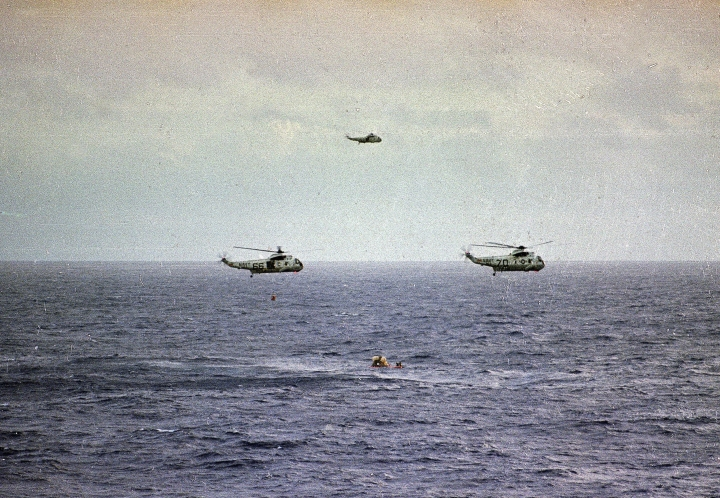 FILE - In this July 24, 1969, file photo, after an eight-day mission on the moon, the Apollo 11 command module lands in the Pacific Ocean and is about to be safely recovered by U.S. Navy helicopters. The Honolulu Star-Advertiser reported Wednesday, July 24, 2019, the 50th anniversary of the astronaut's return to Earth, that the crew hit the atmosphere at 25,000 mph, creating a fireball that was visible to the crew of the waiting recovery aircraft carrier USS Hornet stationed about 900 miles (1,448 kilometers) southwest of Hawaii. (AP Photo, File)