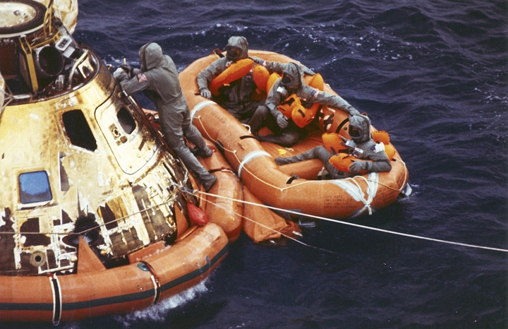 FILE - In this July 24, 1969, file photo from the U.S. Navy, Lt. Clancy Hatleberg closes the Apollo 11 spacecraft hatch as astronauts Neil Armstrong, Michael Collins, and Buzz Aldrin, Jr., await helicopter pickup from their life raft after splashdown in the Pacific Ocean, 900 miles southwest of Hawaii, returning to Earth from a successful lunar landing mission. Hatleberg's mission was to decontaminate the astronauts and their command module, Columbia, immediately following splashdown. The astronauts' trip to the moon concluded with a stay in Hawaii. July 20 marked the 50th anniversary of the moon landing, but after those historic first steps NASA still had to get the three astronauts safely back to Earth - and the waters off Hawaii are where the cone-shaped spacecraft splashed down. (Milt Putnam/U.S. Navy via AP, File)