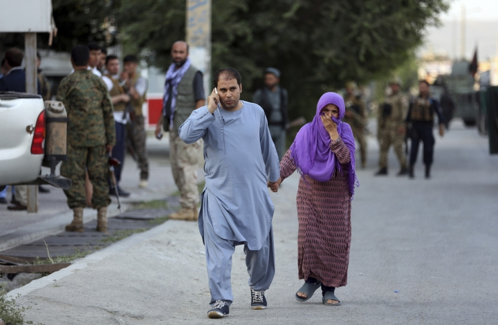 An Afghan family leave the site of a deadly attack in Kabul, Afghanistan, Sunday, July 28, 2019. Afghan officials say the political offices of the president's running mate were hit by a large explosion and stormed by an unknown number of attackers. Nasrat Rahimi, the interior ministry spokesman, said vice-presidential candidate and former intelligence chief Amrullah Saleh survived the attack. (AP Photo/Rahmat Gul)