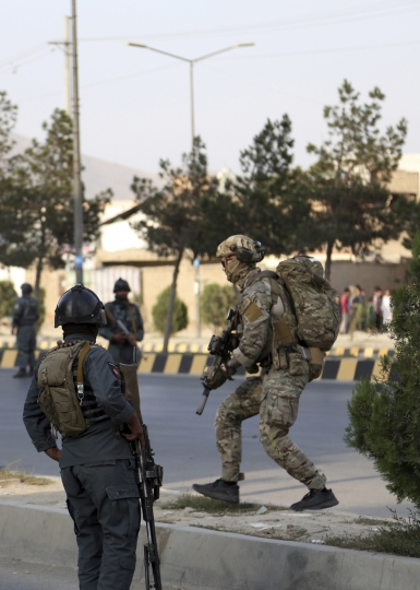 Afghan security personnel and foreign forces secure the site of an attack in Kabul, Afghanistan, Sunday, July 28, 2019. Afghan officials say the political offices of the president's running mate were hit by a large explosion and stormed by an unknown number of attackers. Nasrat Rahimi, the interior ministry spokesman, said vice-presidential candidate and former intelligence chief Amrullah Saleh survived the attack. (AP Photo/Rahmat Gul)