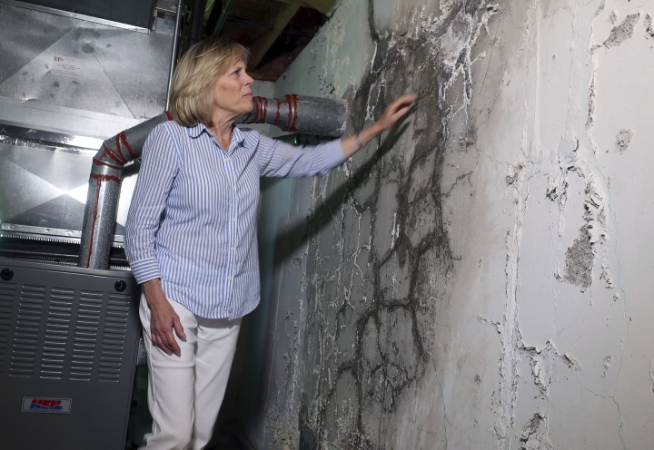 """In this July 1, 2019 photo, Wendy Padula touches the crumbling foundation of her home in Vernon, Conn. The foundation is deteriorating due to the presence of an iron sulfide known as pyrrhotite, often described as """"a slow-moving disaster,"""" which causes concrete to crack and break gradually as it becomes exposed to water and oxygen. After worrying for years about the foundations crumbling beneath their houses, hundreds of suburban homeowners in a large swath of eastern Connecticut are getting help from the state to salvage their properties that had been doomed by bad batches of concrete. (AP Photo/Ted Shaffrey)"""