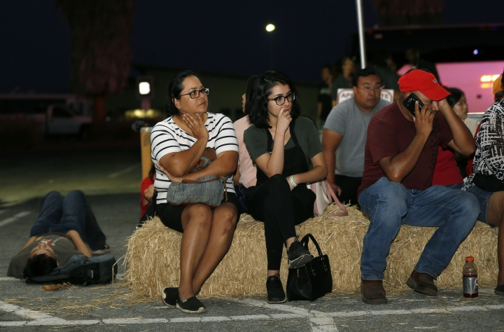 Ana Lilia Cano, left, with daughter Paulina Perez, and Gildardo Leyva, right, wait for relatives at a reunification center at Gavilan College following a shooting at the Gilroy Garlic Festival, in Gilroy, Calif., Sunday, July 28, 2018. (AP Photo/Josie Lepe)