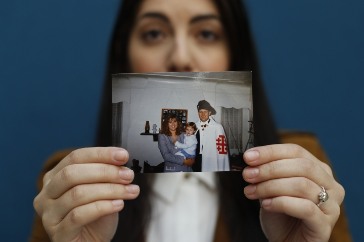 Mary Rose Maher, the daughter of Opus Bono Sacerdotii co-founder Joe Maher, holds a photo from her childhood with her parents in Detroit, Wednesday, June 12, 2019. Opus Bono's finances came under scrutiny after authorities were contacted by a once-loyal employee - Mary Rose - who began questioning the way money was spent. (AP Photo/Paul Sancya)