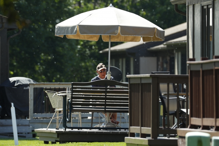 """Father Eduard Perrone reads under an umbrella in Warren, Mich., Friday, June 7, 2019. On Sunday, July 7, the Roman Catholic Archdiocese of Detroit said it had removed Perrone, one of Opus Bono Sacerdotii's co-founders, from public ministry after a church review board decided there was a """"semblance of truth"""" to allegations that he abused a child decades ago.Perrone told the AP that he """"never would have done such a thing."""" (AP Photo/Paul Sancya)"""