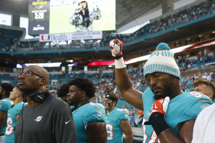 """FILE - In this Aug. 9, 2018, file photo, Miami Dolphins defensive end Robert Quinn (94) raises his right fist during the singing of the national anthem, before the team's NFL preseason football game against the Tampa Bay Buccaneers, in Miami Gardens, Fla. Dallas Cowboys defensive end Robert Quinn says the issue of protesting during the national anthem """"might come up"""" before the season with owner Jerry Jones, who in the past has taken a hardline stance against displays by his players. Quinn joined the Cowboys in an offseason trade. (AP Photo/Wilfredo Lee, File)"""