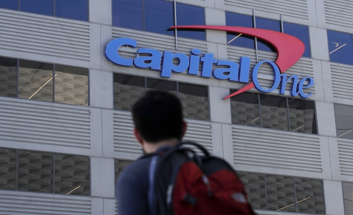 In this July 16, 2019, photo, a man walks across the street from a Capital One location in San Francisco. Capital One says a hacker got access to the personal information of over 100 million individuals applying for credit. The McLean, Virginia-based bank said Monday, July 29, it found out about the vulnerability in its system July 19 and immediately sought help from law enforcement to catch the perpetrator. (AP Photo/Jeff Chiu)