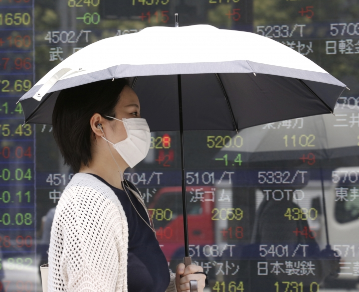 A woman walks by an electronic stock board of a securities firm in Tokyo, Tuesday, July 30, 2019. Shares were mostly higher in Asia on Tuesday as envoys from the U.S. and China prepared to resume trade talks, this time in Shanghai. (AP Photo/Koji Sasahara)