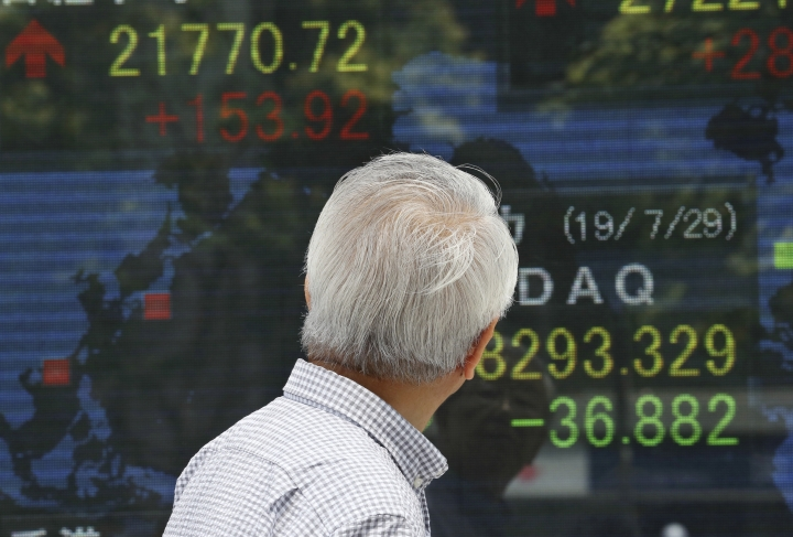 A man looks at an electronic stock board of a securities firm in Tokyo, Tuesday, July 30, 2019. Shares were mostly higher in Asia on Tuesday as envoys from the U.S. and China prepared to resume trade talks, this time in Shanghai. (AP Photo/Koji Sasahara)