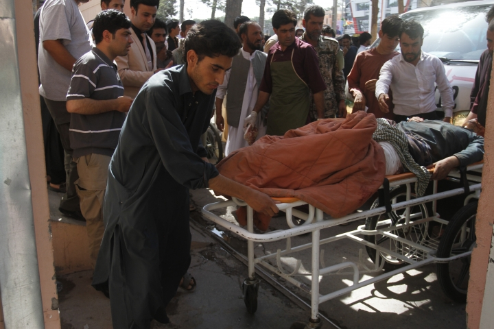 Afghans assist a wounded man in a hospital after a roadside bomb on the main highway between the western city of Herat and the southern city of Kandahar, in Herat, Afghanistan, Wednesday, July 31, 2019. A roadside bomb tore through a bus in western Afghanistan on Wednesday, killing at least 32 people, including children, a provincial official said. (AP Photo/Hamed Sarfarazi)