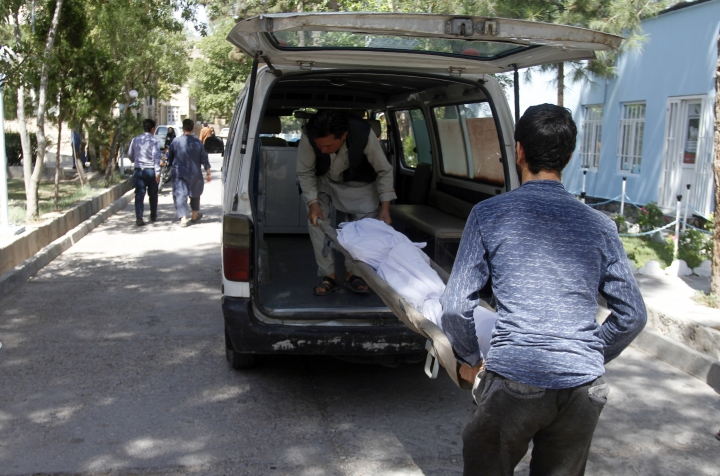 Afghans carry the dead body of a victim in a hospital after a roadside bomb on the main highway between the western city of Herat and the southern city of Kandahar, in Herat, Afghanistan, Wednesday, July 31, 2019. A roadside bomb tore through a bus in western Afghanistan on Wednesday, killing at least 32 people, including children, a provincial official said. (AP Photo/Hamed Sarfarazi)