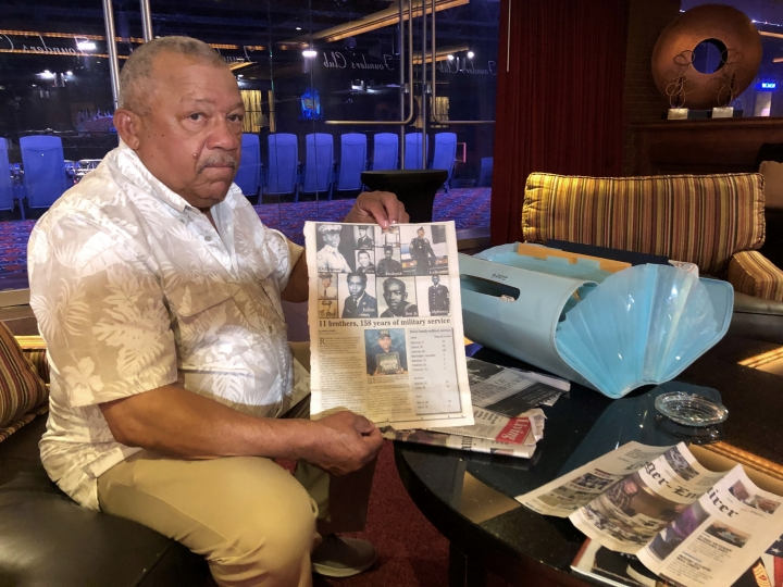 Lebronze Davis shows a reporter newspaper articles about him and his brothers during a reunion at a hotel-casino on Friday, July 12, 2019 in Tunica, Miss. Eleven in all, their combined 158 years of service to the U.S. military make them brothers in arms as well as brothers raised on a family farm in rural Alabama. (AP Photo/Adrian Sainz)