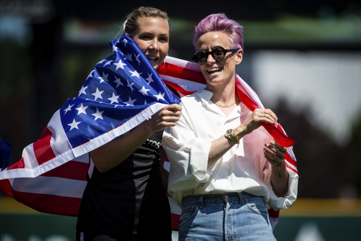 Reign FC midfielder Allie Long, left, and forward Megan Rapinoe, right, wrap themselves in an American Flag during a pregame ceremony honoring the Women's World Cup players at Cheney Stadium, Sunday, July 28, 2019, in Tacoma, Wash. The Reign FC played the Chicago Red Stars in a National Women's Soccer League match. (Joshua Bessex/The News Tribune via AP)