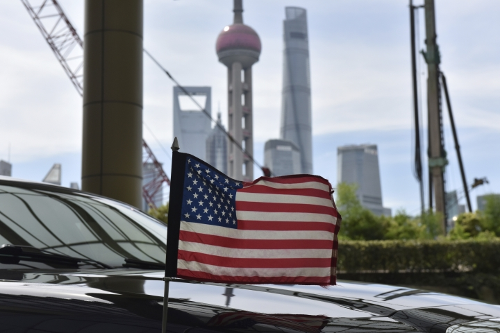 A U.S. flag flies on a U.S. consulate car, with the backdrop of buildings in the Lujiazui financial district, outside a hotel where U.S. trade negotiators are staying, in Shanghai Wednesday, July 31, 2019. (Greg Baker/Pool Photo via AP)