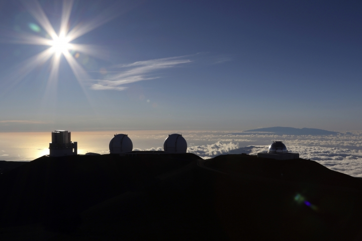 FILE - In this Sunday, July 14, 2019, file photo, the sun sets behind telescopes at the summit of Mauna Kea in Hawaii. The man tasked with trying to find a way out of an impasse over the construction of a giant telescope in Hawaii says he met with Native Hawaiian leaders. But the only issue they reached a consensus on was to meet again. (AP Photo/Caleb Jones, File)
